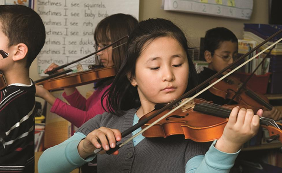 Student practices violin in after school program
