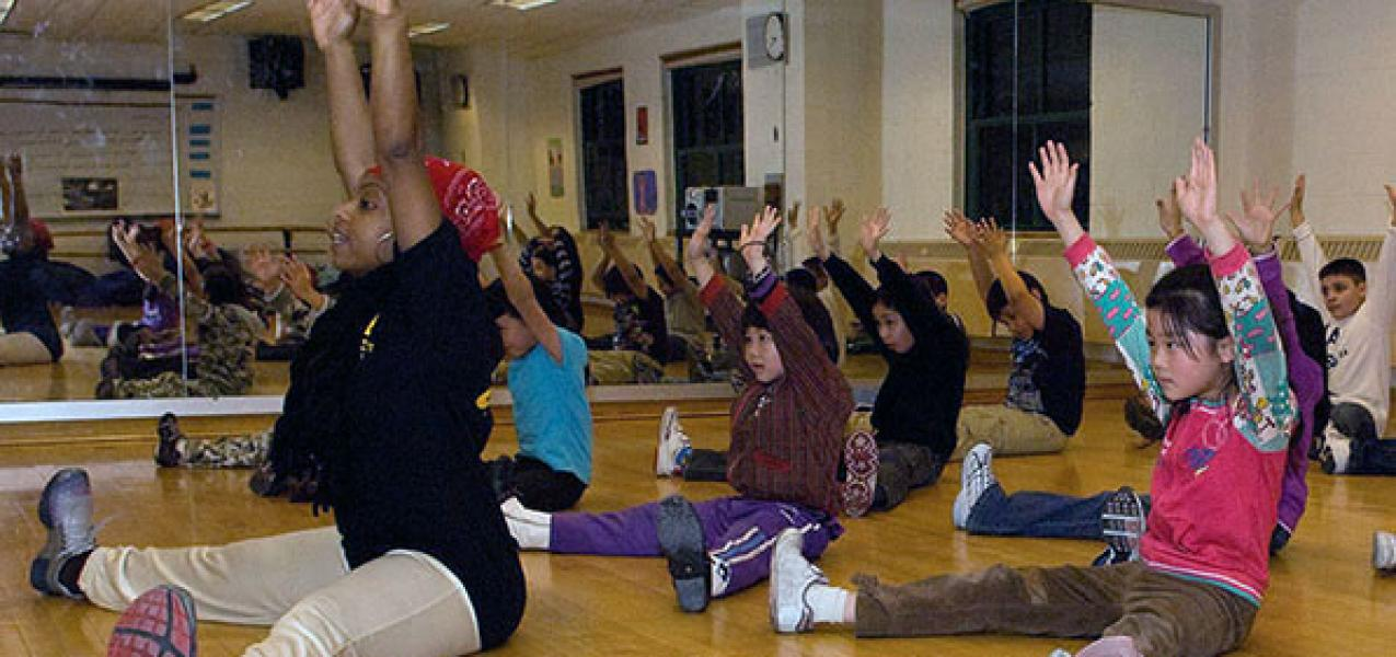 Teacher leads an exercise class for young students