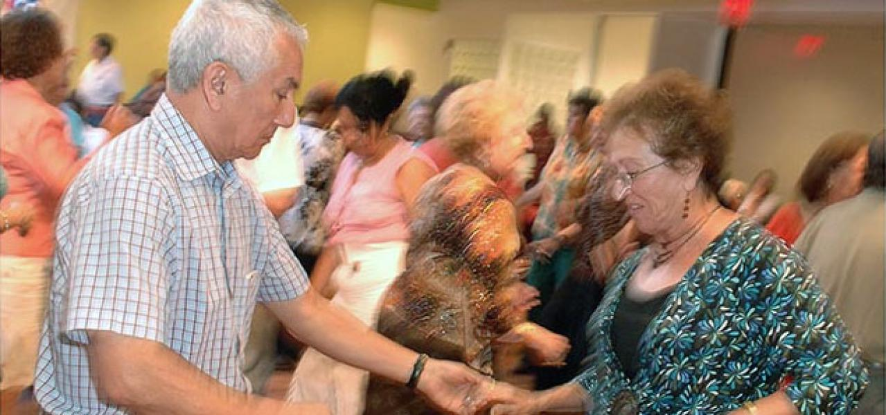 A large crowd of seniors dance at the Center