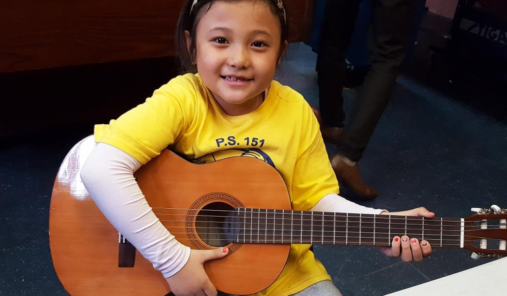 Girl plays guitar in the SCS Cornerstone Program's Music Room