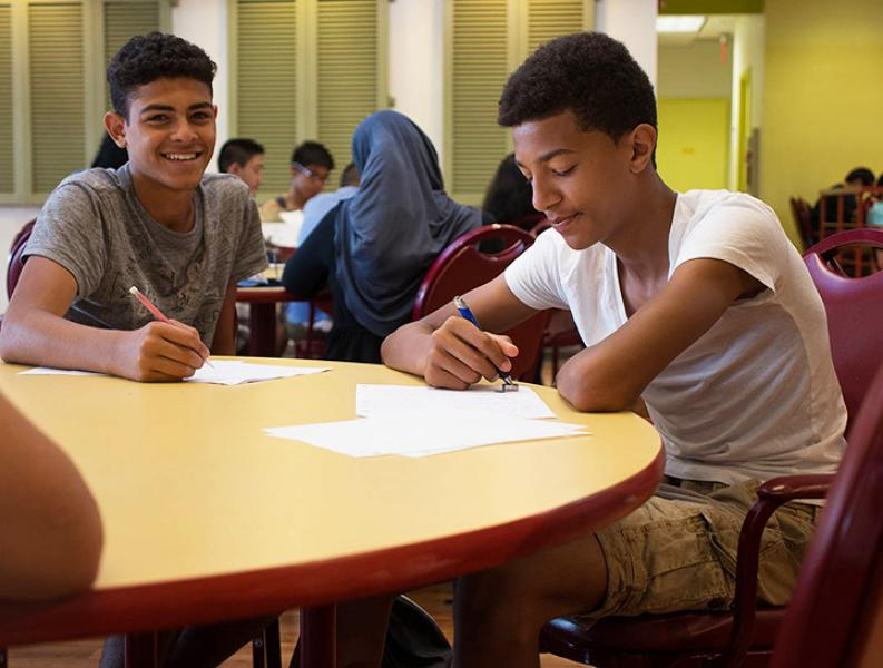 Two male students smile at the camera