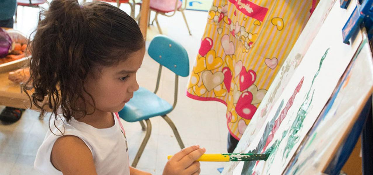 A student in the pre-kindergarten program paints on an easel