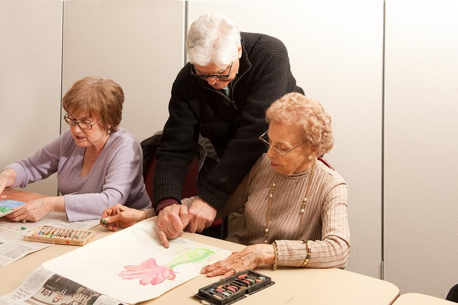 Instructor guides senior participants of the Art Class at the Center