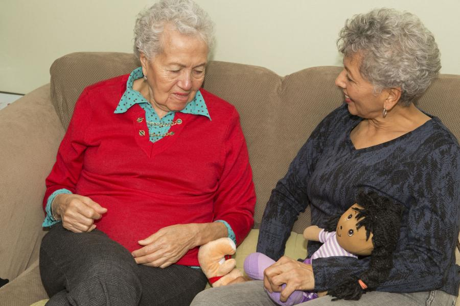 A woman with Alzheimer's disease interacts with her family caregiver
