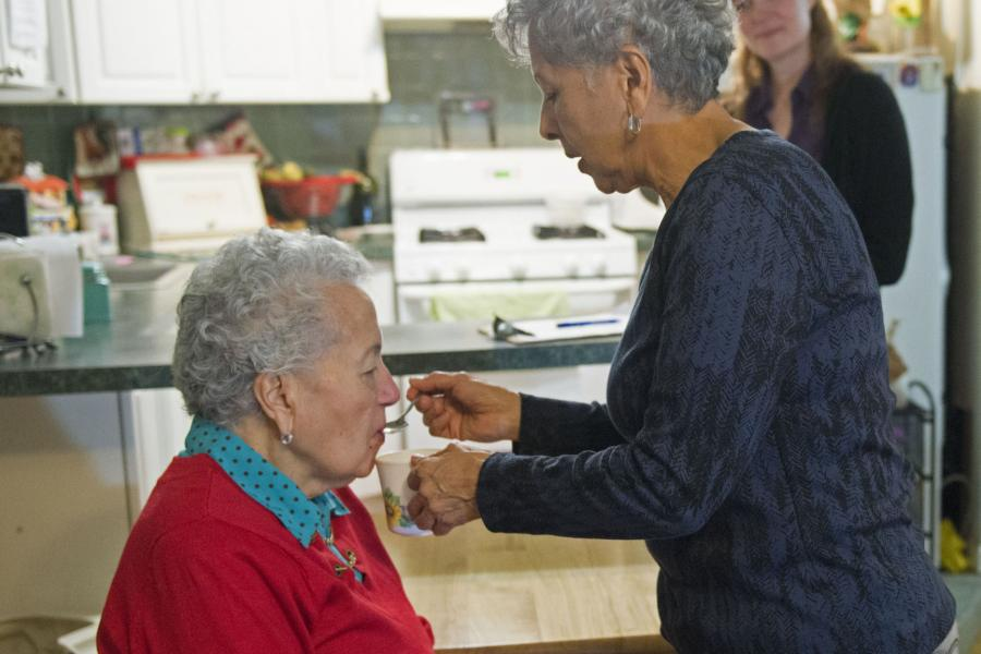 Caregiver feeds mother while supportive staff looks on.