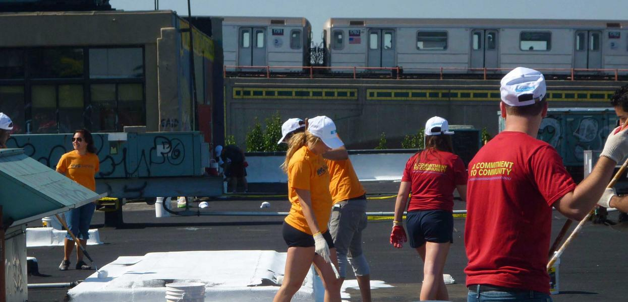 A group of volunteers paint the roof of Sunnyside Community Services