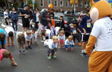 Children participating in the 3rd Annual Sunnyside Post Mile Run warm up before their sprint