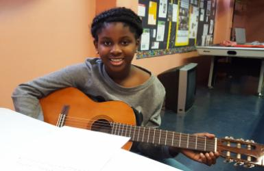 Smiling girl plays guitar in the Music Room at SCS Cornerstone Program at Woodside Houses