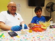 Senior and youth participant show off healthy snack they made