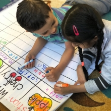 Photo of two young children writing with markers