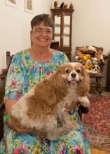 A senior member strokes the head of therapy dog