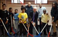 Children with hockey sticks and NYC Council Majority Speaker Jimmy Van Bramer during a visit